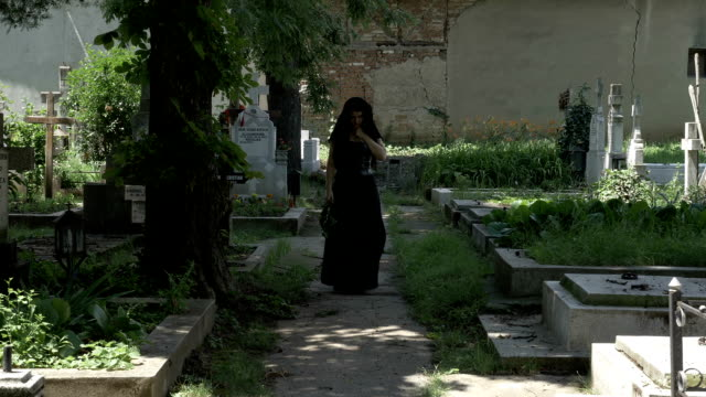 Grieved widow filled with sorrow leaving from departed husband grave walking in cemetery alley video