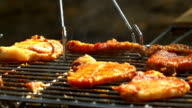 Grilled pork steaks over flames and coals, on the brazier, slush and turn, close up, side view video