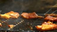 Grilled pork steaks over flames and coals, on the brazier, taking away by prick with a fork, close up, side view video