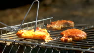 Grilled pork steaks over flames and coals, on the brazier, taking away by blade, fork video