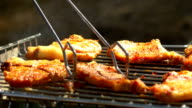 Grilled pork steaks over flames and coals, on the brazier, turn slices, close up, side view video