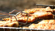 Grilled steaks over flames and coals, on the brazier, turn slices, close up video