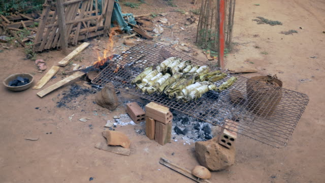 Grilling banana rice cakes over open fire and makeshift barbecue video
