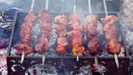 Grilling barbecue meat on wood coal. Man turns skewers video