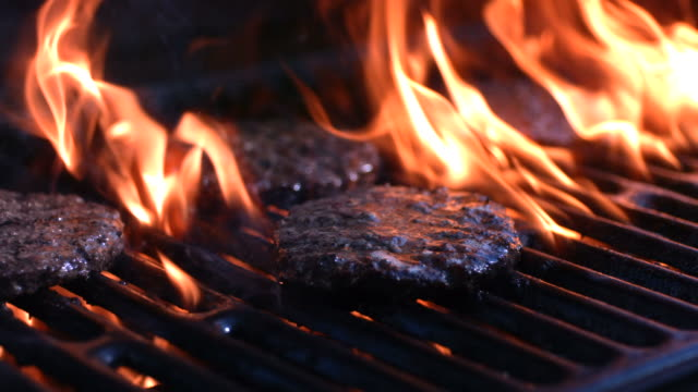 Grilling hamburgers, slow motion video