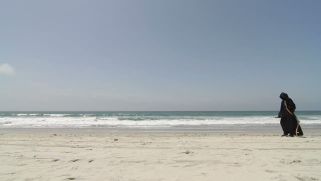 grim reaper walking on the beach RtoL video