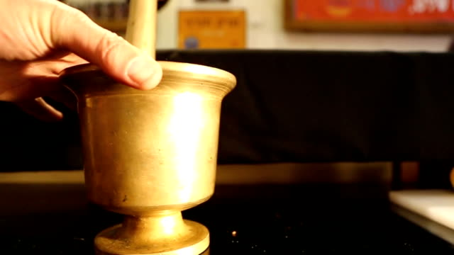 Grinding Spices in an Old Fashion Metal Mortar and pestle video