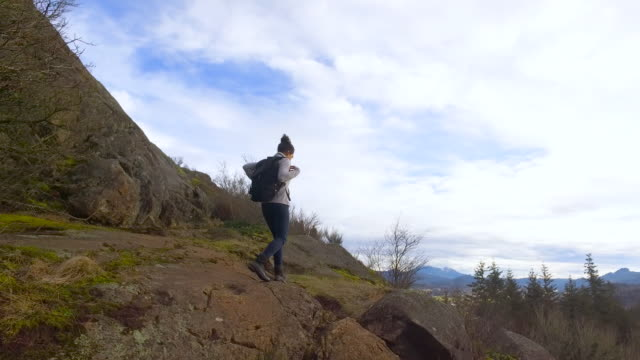 Gritty young woman hiking solo video