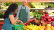 Grocery store worker helps woman shopping for produce video