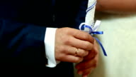 Groom and bride hold thick white candles in their hands during the ceremony video