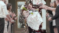 SLO MO Groom carrying bride from church in flower shower video
