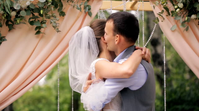 Groom embraces and kisses beloved after wedding ceremony video