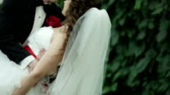 Groom holds his bride in his arms . video