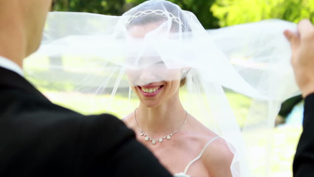 Groom lifting veil off beaming brides face video