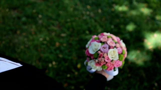 Groom lifts up a wedding bouquet in his hand. Beautiful wedding bouquet of fresh flowers video