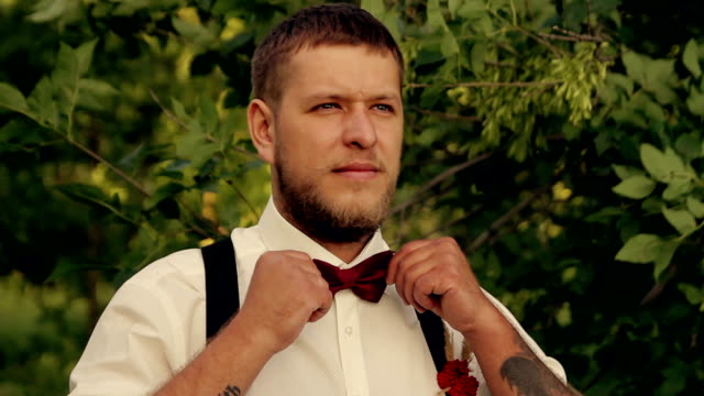 groom wears a tie in the park at sunset video