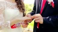 groom wears the ring on the bride's hand close-up, registration in the park video