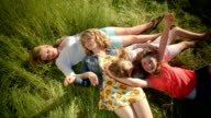 Group Of 4 Girls Lay In A Field, They Tickle Each Other And Play With Grass video