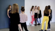 Group of attractive girls trains in posing before going on photo session video