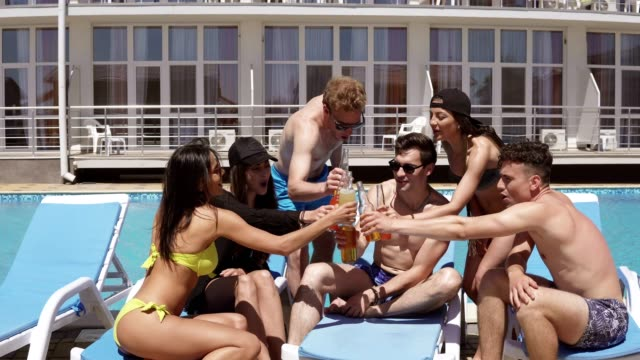Group of beautiful young friends in swimsuits drinking cocktails with cheers and having fun sitting by the swimming pool. Shot in 4k video