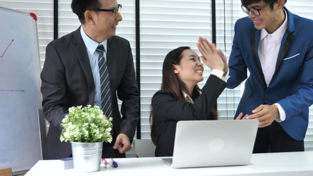 Group of business people cheering and high-five in office meeting video
