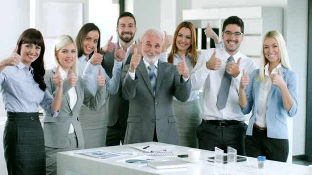 Group of business people holding up their thumbs video