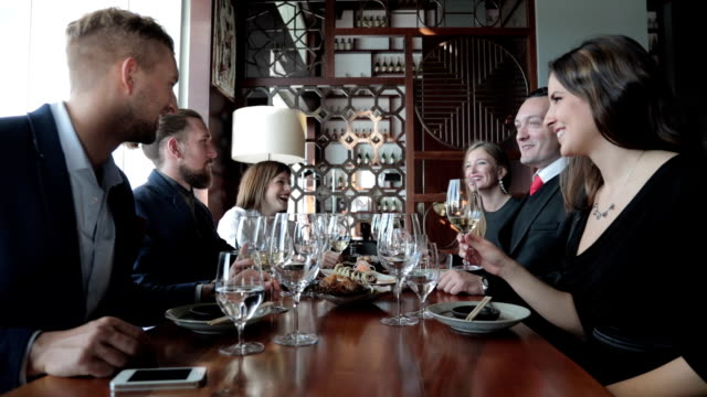 Group of business people toasting at restaurant video
