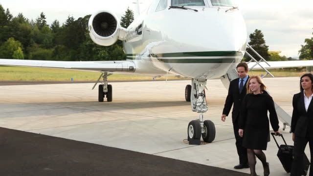 Group of business people walk by jet video