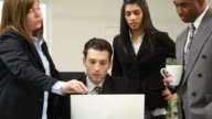 Group of businesspeople look at computer together video