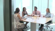 Group of businesspeople sitting around desk having meeting.Shot on Sony FS700 at frame rate of 25fps video