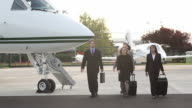 Group of businesspeople walk at airport video