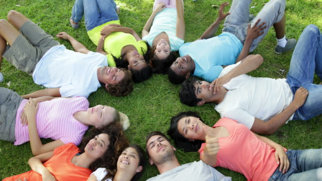 Group of casual young friends lying in a circle video