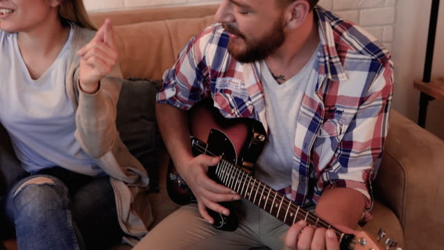 Group of cheerful friends having fun while their friend is playing a guitar at home. video