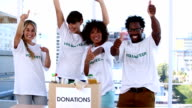 Group of cheerful volunteers raising their arms video