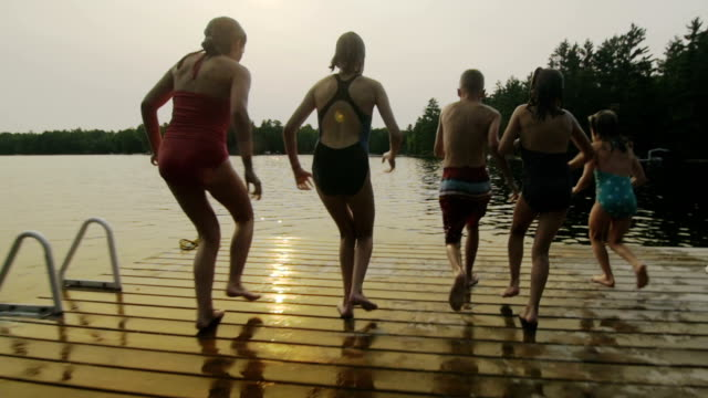 Group of children jumping off dock video