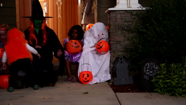 Group of children look at Halloween candy video