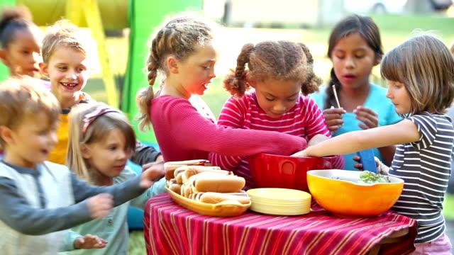 Group of children run up to table of food and eat video