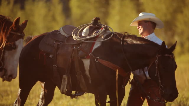 Group of cowboys saddle up and prepare for ride video