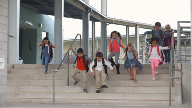 A group of energetic elementary school kids leaving school video