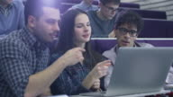 Group of female and male students are sitting in a college classroom and looking at a laptop computer. video