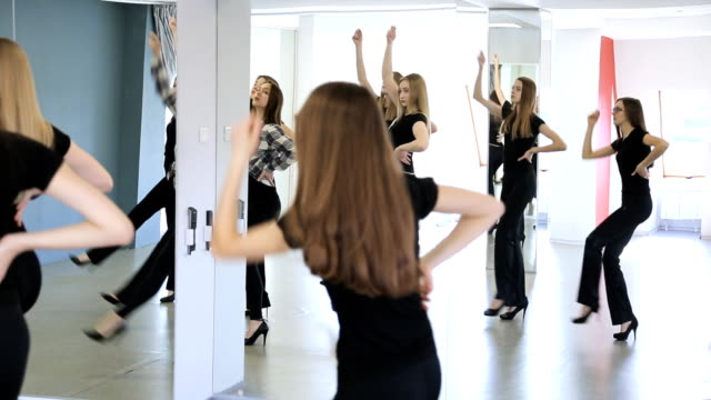 Group of female models in black are learning dance video
