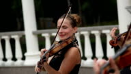 Group of female violinists play a melody on the street video
