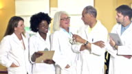 Group of five multi-ethnic doctors in white lab coats video