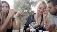 Group of four happy men and women friends smile, laugh, eat croissants during italian breakfast in natural rural scenic outdoor during summer sunny day morning in tuscany - slow-motion HD video footage video