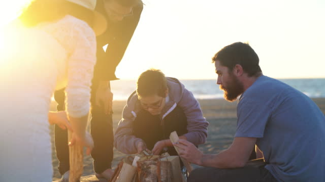 Group of friends at the beach trying to start a fire video