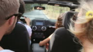 Group Of Friends Driving In Open Top Car Along Country Road video