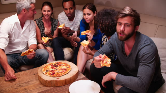 Group Of Friends Eating Takeaway Pizza And Watching TV video