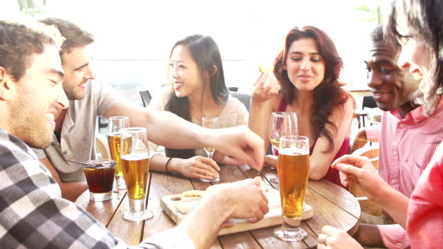 Group of friends enjoy drinks and snacks at rooftop bar.Shot on Sony FS700 in PAL format at a frame rate of 25fps video