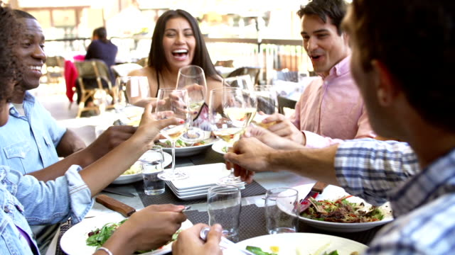 Group Of Friends Enjoying Meal At Outdoor Restaurant video