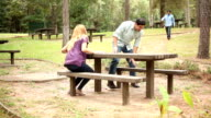 Group of friends gathering at picnic table in park. video